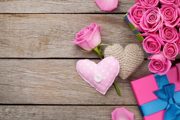 Valentinstag hintergrund mit geschenkbox voller rosa rosen und handgemachten spielzeugherzen Premium Fotos