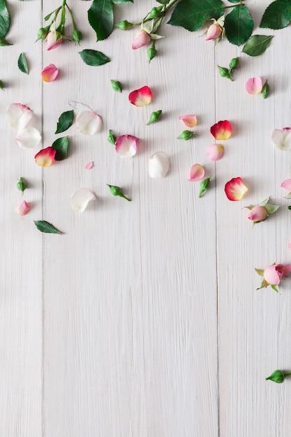 Valentinstag hintergrund, rosa rosenblumen und blütenblätter verstreut auf weißem rustikalem holz, draufsicht mit kopienraum. glückliches liebestagmodell Premium Fotos