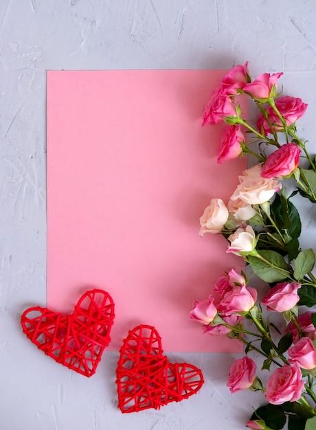 Valentinstag hintergrund. rosen auf pastellrosahintergrund und einem roten herzen. valentinstag . flache lage, draufsicht, kopienraum. Premium Fotos