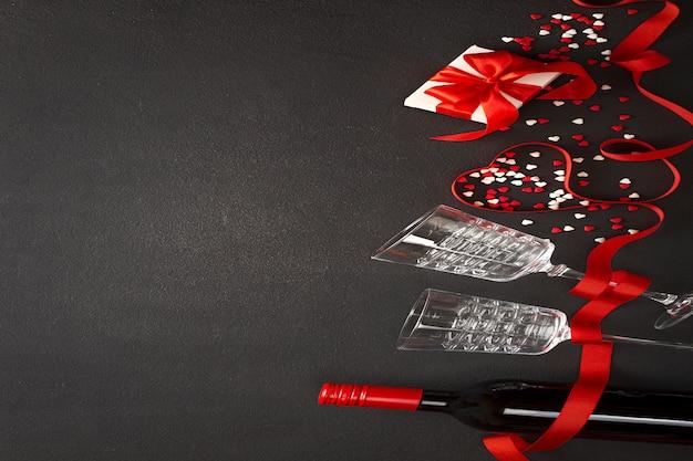 Valentinstag hintergrund. wein, herzen, geschenk, gläser auf dunklem beton Premium Fotos