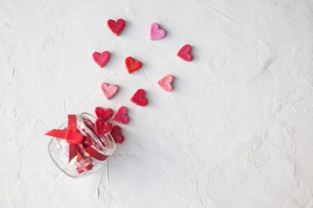 Valentinstag-konzept. glas mit herzen von süßigkeiten auf hellem hintergrund, ansicht von oben Premium Fotos