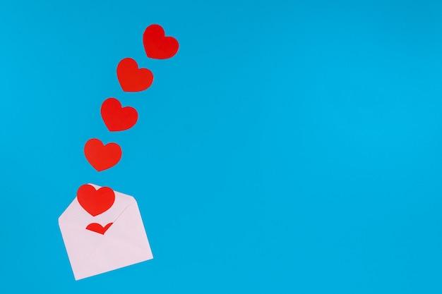 Valentinstag konzept. rotes herz springt aus einem hellrosa umschlag heraus Premium Fotos