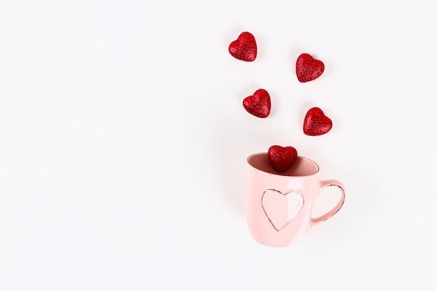 Valentinstag-layout. rosa becher mit abgehenden herzen auf einem weißen hintergrund. valentinstag Premium Fotos
