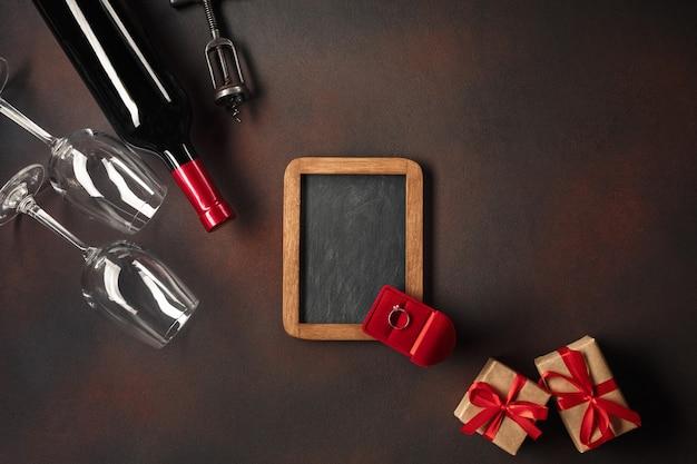 Valentinstag mit herzen, wein, gläsern, geschenken, einer schachtel in form eines herzens und eines korkenziehers Premium Fotos