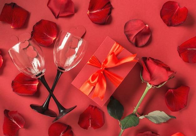 Valentinstag muttertag konzept rote geschenkbox blumen rosenblätter weingläser flach liegen Premium Fotos