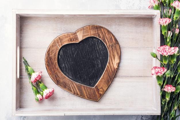 Valentinstag oberfläche mit vintage schiefer kreidetafel in herzform und rosa nelkenblumen mit kopienraum für text. von oben betrachten Premium Fotos