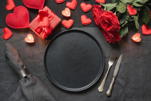 Valentinstag oder geburtstagsessen. romantisches gedeck mit rotrose auf schwarzer leinentischdecke. Premium Fotos