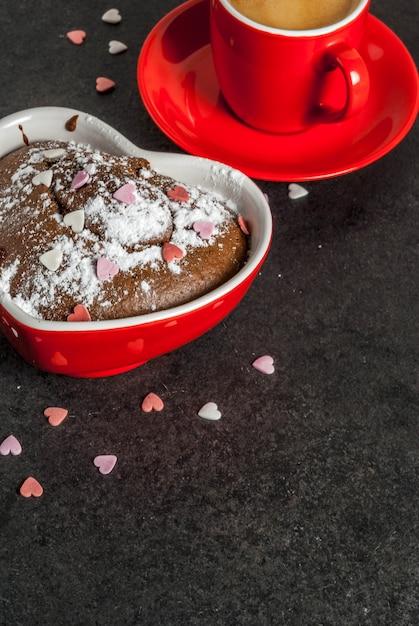Valentinstag, rote kaffeetasse und schokoladenbecherkuchen oder schokoladenkuchen mit puderzucker und schatz formten besprüht, schwarzes, copyspace Premium Fotos
