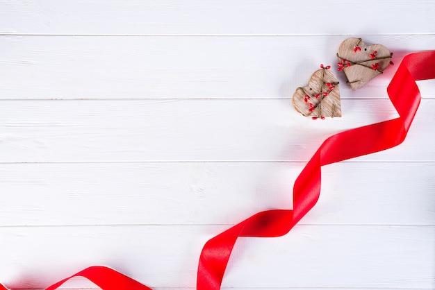Valentinstag. rotes band und zwei hölzerne herzen auf weißem hintergrund. Premium Fotos