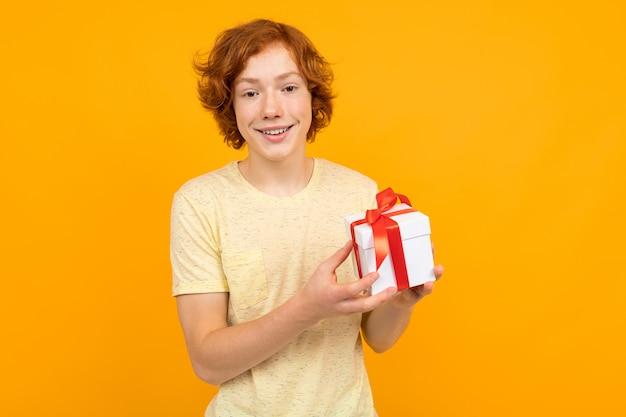 Valentinstag . rothaariger jugendlicher mit einem geschenk in seinen händen auf einem gelb Premium Fotos