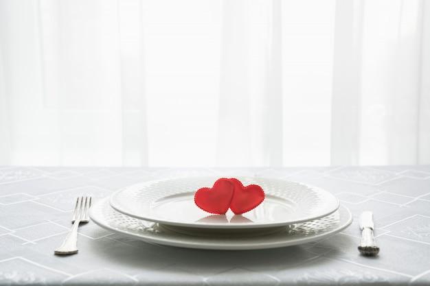 Valentinstag tischgedeck mit zwei herzen. platz für text. einladung zu einem date. Premium Fotos