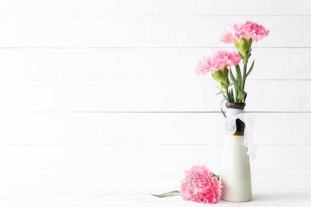 Valentinstag und liebeskonzept. rosa gartennelkenblume im vase auf hölzernem. Premium Fotos