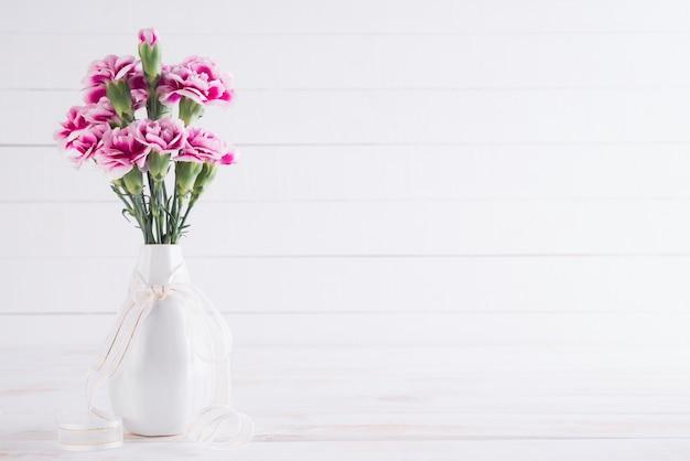 Valentinstag und liebeskonzept. rosa gartennelkenblume im vase Premium Fotos