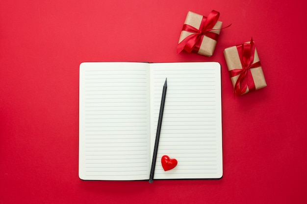 Valentinstag verspotten. öffnen sie notizbuch mit roten herzen und geschenkboxen, auf rotem hintergrund, kopienraum für text. Premium Fotos