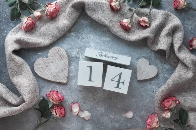 Valentinstagfeier, flach lag mit holzkalender, rosa rosen und holzherzen auf dunkelgrauem hintergrund. Premium Fotos