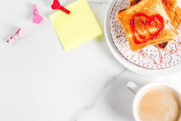 Valentinstagfrühstücksidee mit kaffeetasse, toastbrot mit roter erdbeermarmelade Premium Fotos