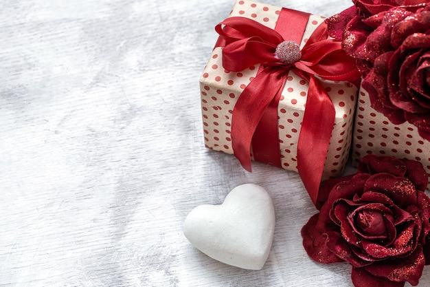 Valentinstaggeschenk mit dekorativen rosen und weißem herzen auf hellem hintergrund kopieren raum. Kostenlose Fotos