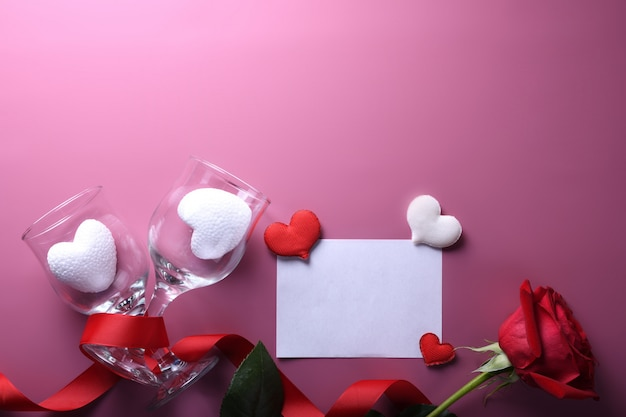 Valentinstaghintergrundgrußkarten-liebessymbole, rote dekoration mit glasherz-rosengeschenken auf rosa hintergrund. draufsicht mit kopienraum und -text flache lage Premium Fotos