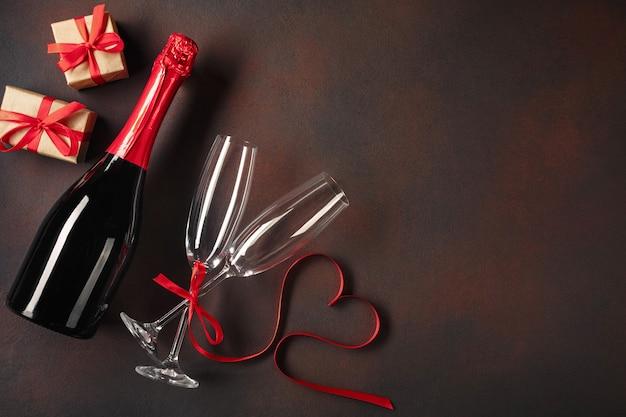 Valentinstagkarte mit gläsern champagner und geschenkboxen. Premium Fotos