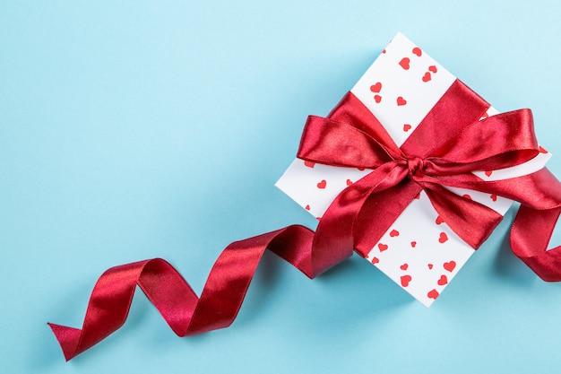 Valentinstagkonzept - geschenk mit herzen und rotem band, blaues backgound, draufsicht Premium Fotos