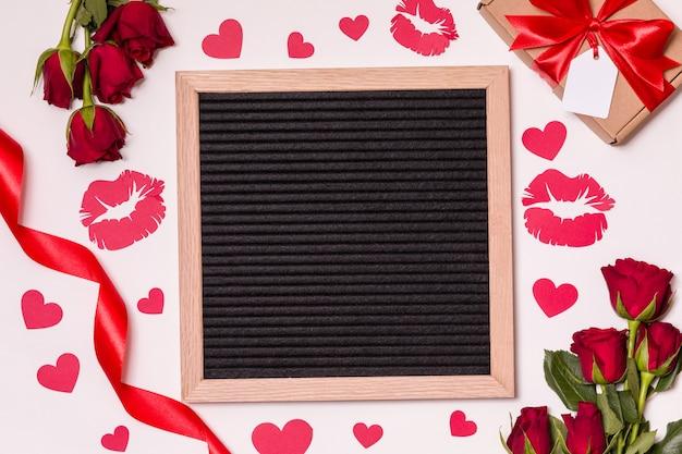 Valentinstagkonzept, leeres briefbrett auf hintergrund mit roten rosen, küsse und herzen. Premium Fotos