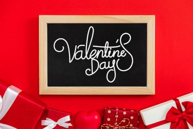 Valentinstagtext mit geschenkboxen auf rotem hintergrund Premium Fotos