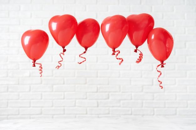 Valentinstagzusammensetzung mit roten ballons auf weiß Premium Fotos