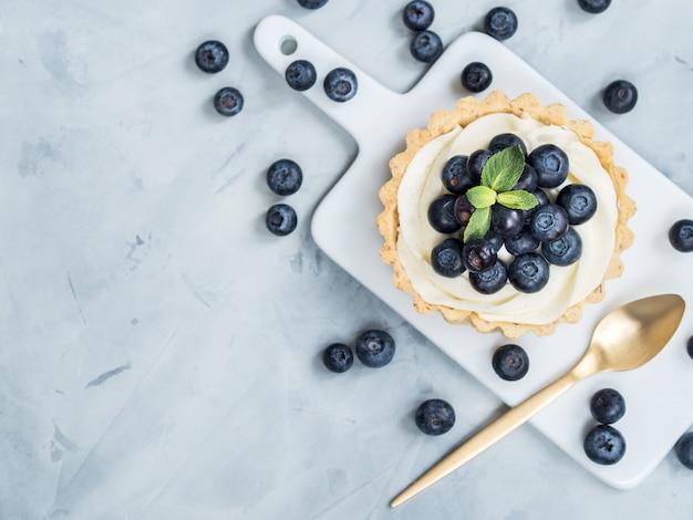 Vanille tartlets mit blaubeerbeeren auf hellem hintergrund. Premium Fotos