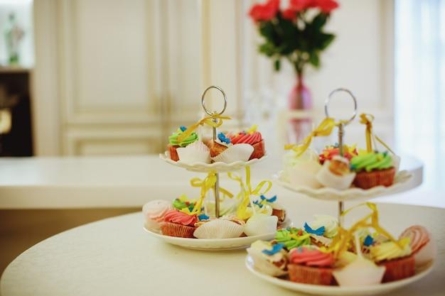 Vanillebohnen-minikleine kuchen verziert mit cyan-blauen und rosa süßigkeitsperlen auf einem klaren abgestuften behälter auf einer nachtischtabelle. süße tabelle mit frucht, kekse. hochzeitsverpflegung. schokoriegel auf party. köstliche kleine kuchen Premium Fotos