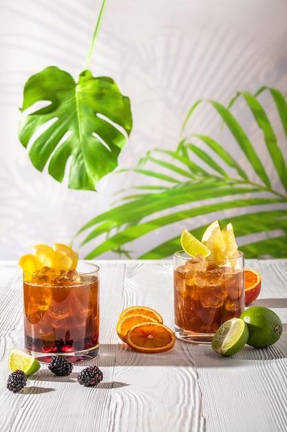 Variationen des espresso-tonics auffrischungsgetränks mit verschiedenen früchten und sirupen auf holztisch unter morgensonne Premium Fotos