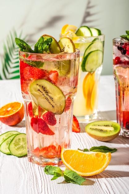 Variationen von limonaden mit verschiedenen früchten und sirupen auf holztisch unter morgensonne Premium Fotos