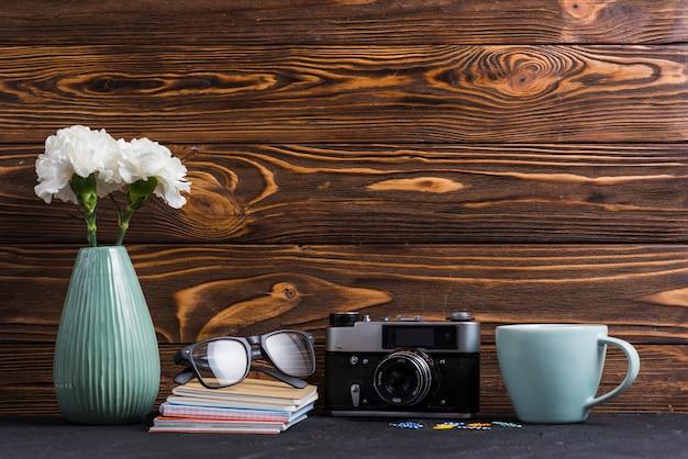 Vase; bücher brille; büroklammer; tasse und retro-kamera auf schwarzem schreibtisch vor hölzernen hintergrund Kostenlose Fotos