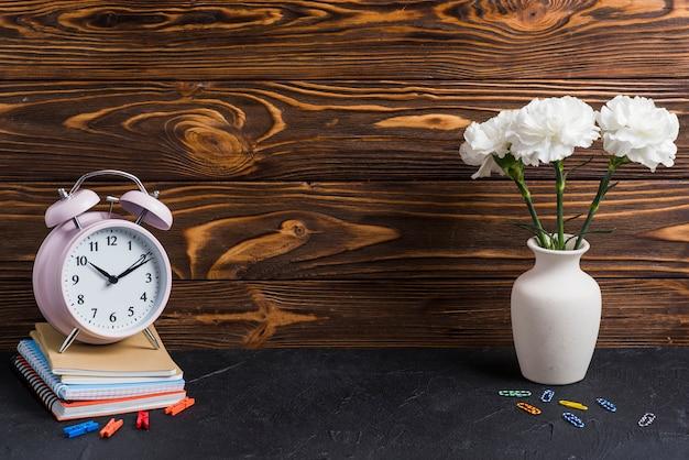 Vase; bunte büroklammer; wäscheklammer und wecker auf notebooks über dem schwarzen hintergrund gestapelt Kostenlose Fotos