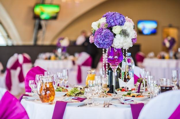 Vase mit blumen auf einem runden tisch serviert, abendessen in einem luxuriösen restaurant Premium Fotos