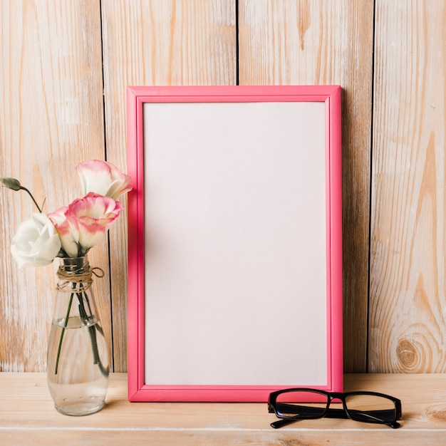 Vase und brille in der nähe des weißen rahmens auf dem schreibtisch Kostenlose Fotos