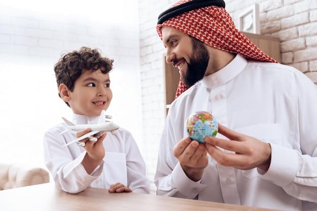 Vater arab erzählt seinem sohn vom flugzeugflug. Premium Fotos