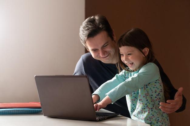 Vater arbeitet zu hause im büro, während seine kleine tochter ihn behindert Premium Fotos