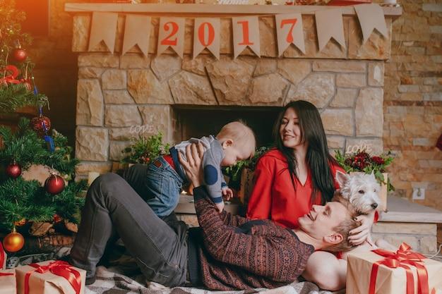 Vater auf dem boden liegend mit einem kamin im hintergrund, während sein baby aufrichten und die mutter schaut sie lächelnd Kostenlose Fotos