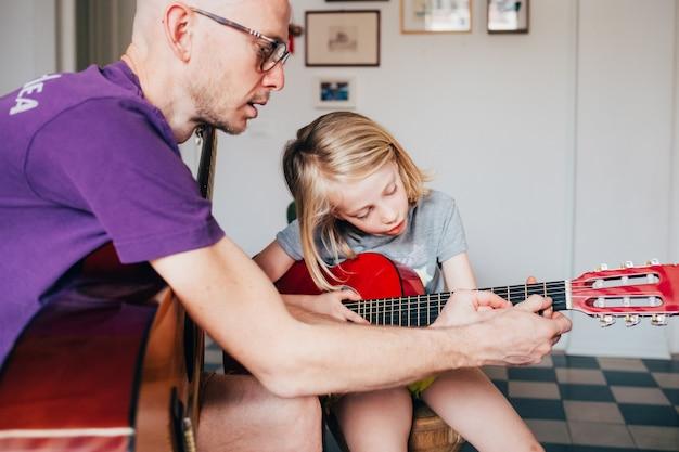 Vater bringt seiner tochter das gitarrenspielen bei Premium Fotos