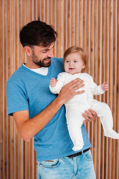 Vater, der baby mit hölzernem hintergrund hält Kostenlose Fotos