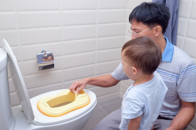 Vater, der schläfrigen sohn trainiert, um toilette im badezimmer zu benutzen, asiatischer kleinkindjunge, der auf toilette mit kinderbadezimmerzubehör sitzt Premium Fotos