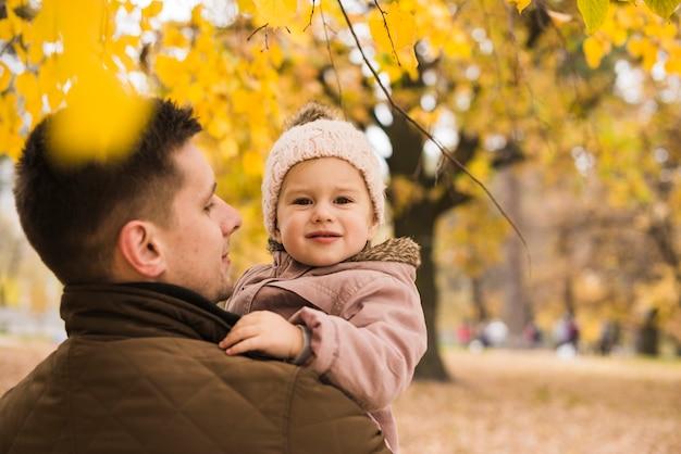 Vater, der tochter in den händen im herbstpark hält Kostenlose Fotos