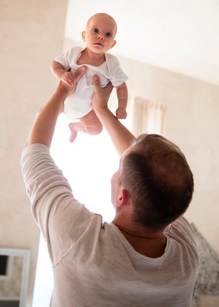 Vater, der zuhause mit baby spielt Kostenlose Fotos