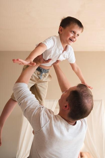 Vater, der zuhause mit kleinkind spielt Kostenlose Fotos