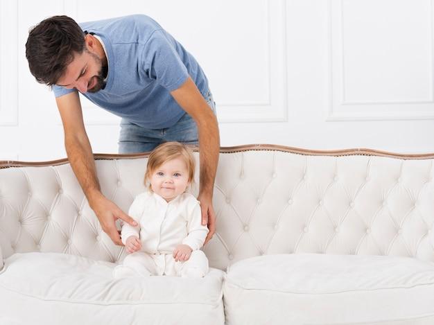Vater hält baby auf dem sofa Kostenlose Fotos