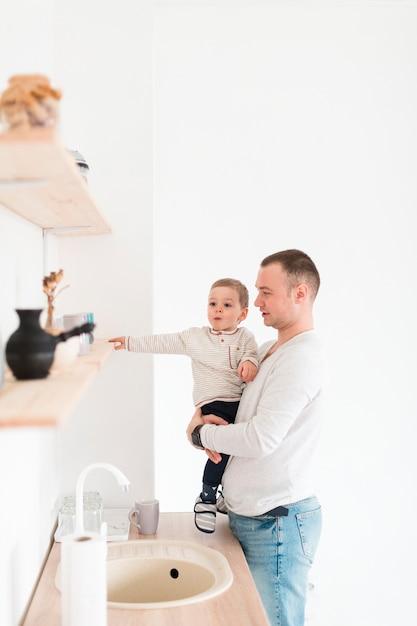 Vater hält kind, während in der küche mit kopienraum Kostenlose Fotos