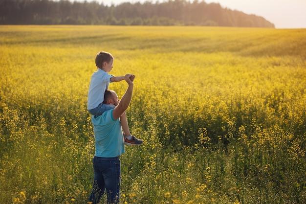 Vater hält seinen sohn auf den schultern und steht Premium Fotos