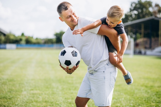 Vater mit dem sohn, der fußball am feld spielt Kostenlose Fotos