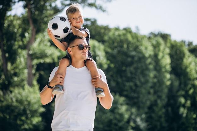Vater mit dem sohn, der fußball am strand spielt Kostenlose Fotos