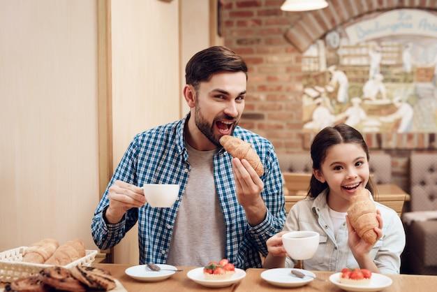 Vater mit der tochter, die kuchen in der cafeteria isst. Premium Fotos